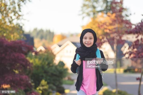 arabisch-amerikanische mädchen zu fuß zur schule - kopftuch stock-fotos und bilder