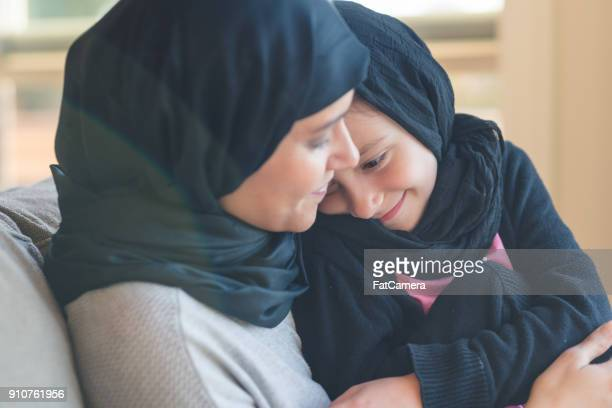 arab-american woman holds her young daughter - muslim mother stock pictures, royalty-free photos & images