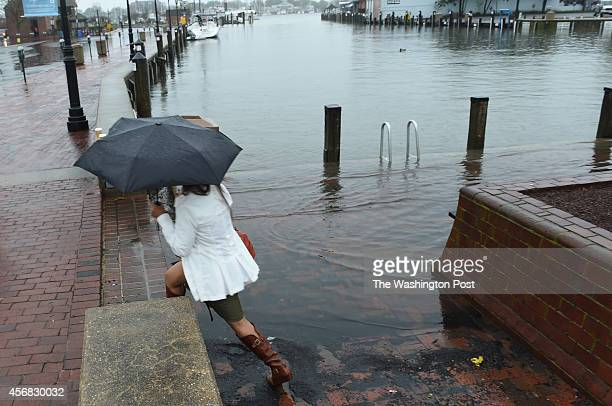 Arabella Ancheta of Bakersfield CA steps around the flooded sidewalk at City Dock in Annapolis as a massive storm system drops heavy rains on the DC...