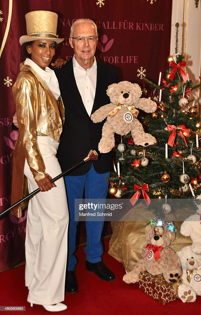 Arabella Kiesbauer (L) and Franz Beckenbauer pose for a photograph during the Energy For Life christmas ball for children at Hofburg Vienna on December 16, 2014 in Vienna, Austria.