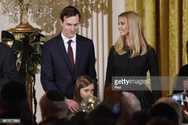 Arabella Kushner lights the menorah as Jared Kushner and Ivanka Trump look on during a Hanukkah Reception in the East Room of the White House on...