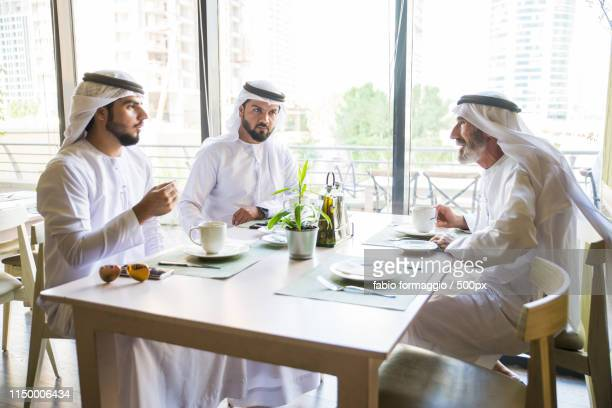 arabian businessmen at restaurant cafè - man in dress stock photos and pictures