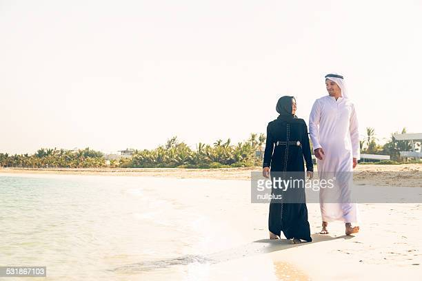 arabian couple walking on the beach