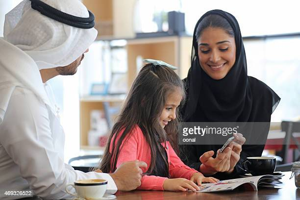 arabian family enjoying cafe break time - qatar stock pictures, royalty-free photos & images