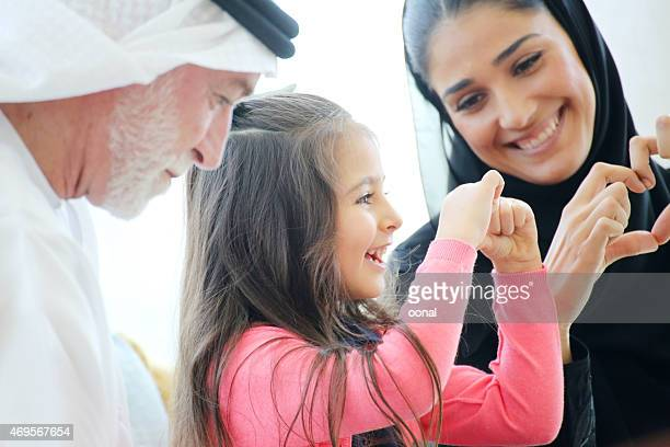 arabian family making heart symbols with hands in a cafe - saudi stock pictures, royalty-free photos & images