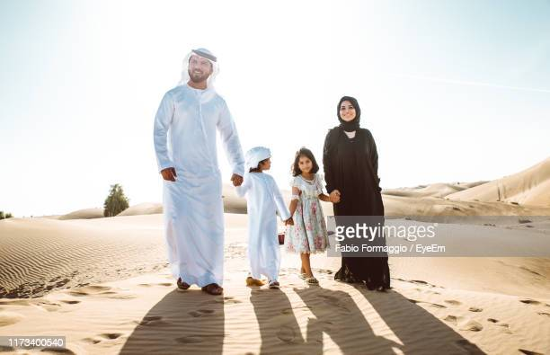 arabian family standing at desert against sky - two generation family stock pictures, royalty-free photos & images