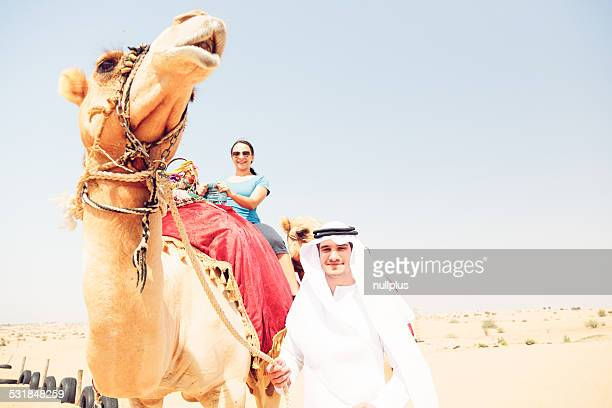 arabian man and tourist riding a camel