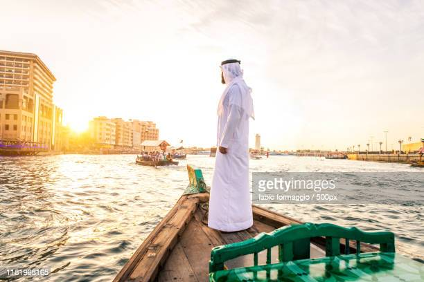 arabian man on abra boat on creek's canal - canal stock pictures, royalty-free photos & images