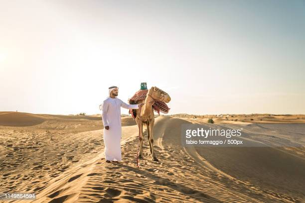 arabian man with camel in the desert - qatar desert stock photos and pictures