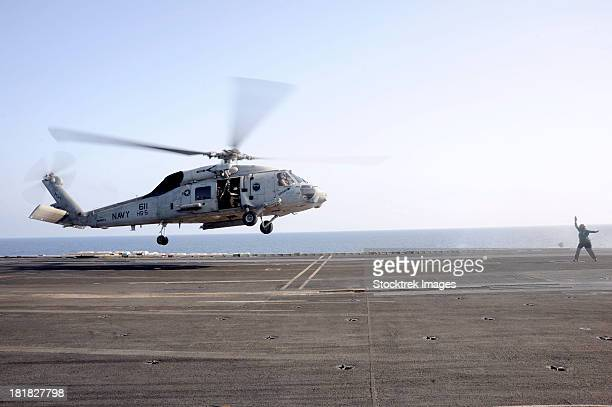 arabian sea, march 22, 2013 - a helicopter landing signalman directs an sh-60f sea hawk helicopter onto the flight deck of the aircraft carrier uss dwight d. eisenhower. - aircraft carrier stock pictures, royalty-free photos & images