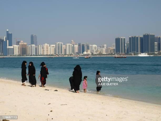 Arabian women in abaya walking by the shore, Corniche, Abu Dhabi.