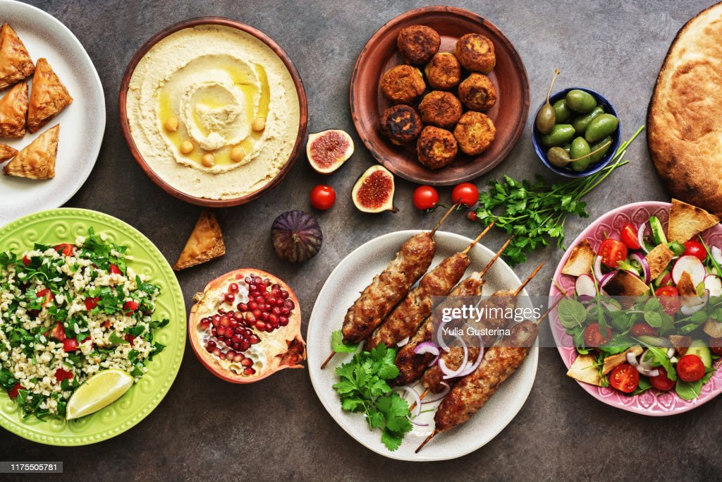 Arabic and Middle Eastern dinner table. Hummus, tabbouleh salad, Fattoush salad, pita, meat kebab, falafel, baklava, pomegranate. Set of Arabian dishes.Top view, flat lay : Stock Photo