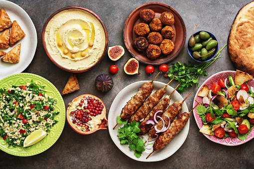 Arabic and Middle Eastern dinner table. Hummus, tabbouleh salad, Fattoush salad, pita, meat kebab, falafel, baklava, pomegranate. Set of Arabian dishes.Top view, flat lay 1175505781