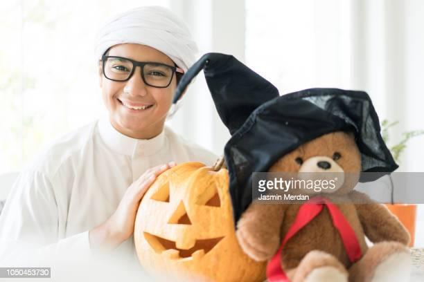 arabic boy with halloween pumpkin lantern - 宗教的なベール ストックフォトと画像