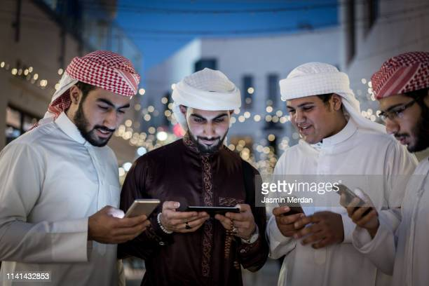 arabic boys with smartphones - headdress stock pictures, royalty-free photos & images