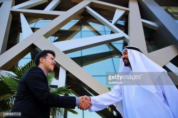 arabic business and businessman shaking hands - dar cartas imagens e fotografias de stock