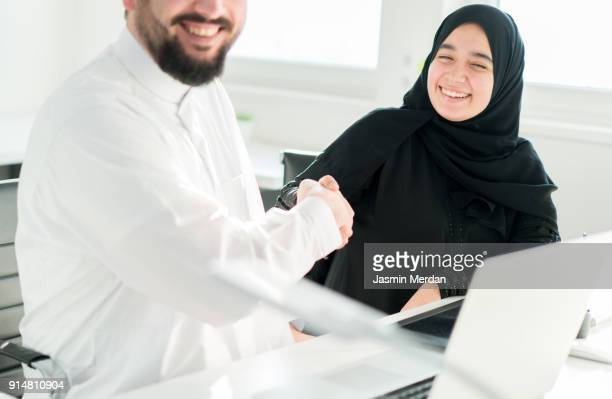 Arabic business male and female closing the deal with handshaking