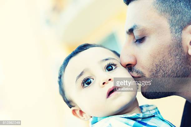 Arabic father kissing his child