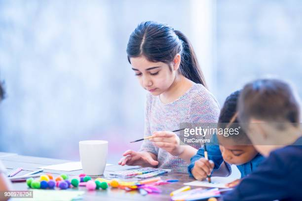 arabic girl painting with friends - art and craft stock pictures, royalty-free photos & images