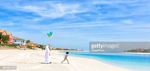Arabic  Grandfather and child walking on the Palm Jumeirah Beach