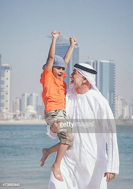 Arabic grandfather holding grandson in the arm at beach