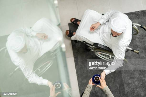 arabic man in wheelchair at home - persons with disabilities stock pictures, royalty-free photos & images