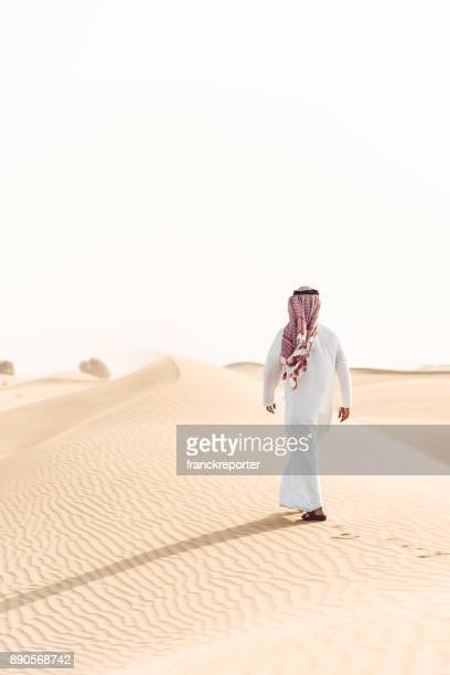 arabic man walking alone in the desert - qatar desert stock photos and pictures