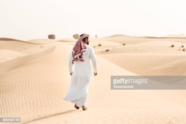 arabic man walking alone in the desert - saudi stock pictures, royalty-free photos & images