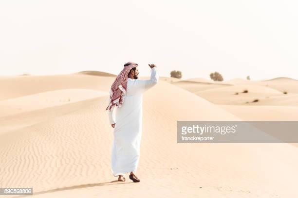 hombre árabe que caminar solo en el desierto - qatar fotografías e imágenes de stock