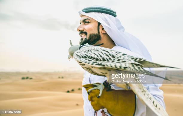 arabic man with traditional emirates clothes walking in the dese - kaffiyeh stock pictures, royalty-free photos & images