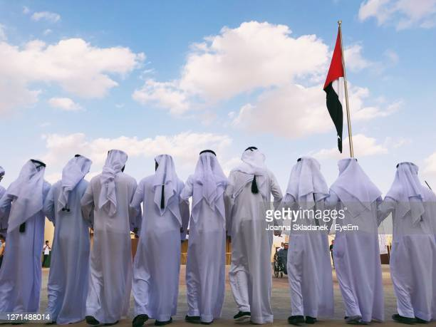 arabic men performing traditional dance in the united arab emirates - parade stock pictures, royalty-free photos & images
