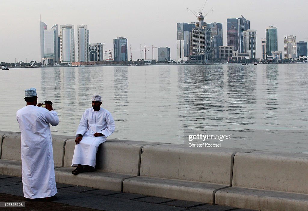 Arabic men photograph thereselfs alongside the skyline of the West Bay area in Doha on January 4, 2011 in Doha, Qatar. The International Monetary Fund (IMF) recently reiterated its projection for the Qatari economy with predictions of double digit growth for 2010 and 2011. Though natural gas and petroleum production are still the biggest two single sources of income, the non-energy sector overtook oil and gas in Qatari GDP for 2009. The FIFA world cup 2022 will takes place in Qatar.