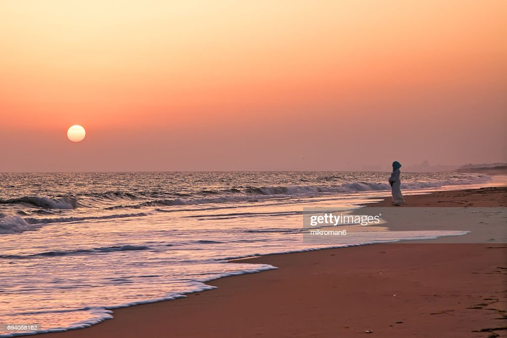 Arabic Muslim Pregnant Woman looking towards sunset with the hope for the future. : Stock Photo