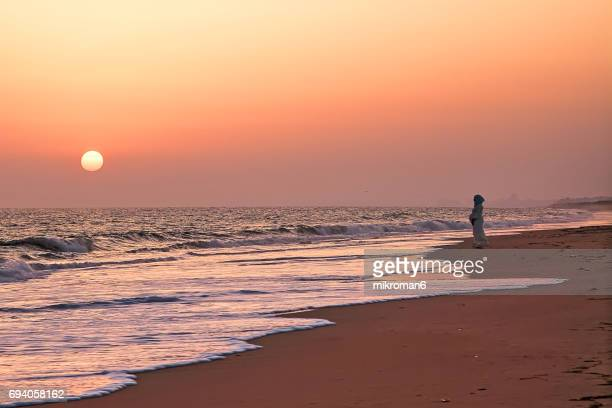 Arabic Muslim Pregnant Woman looking towards sunset with the hope for the future.
