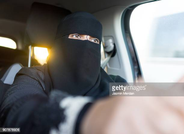 Arabic Muslim woman with veil and scarf driving car