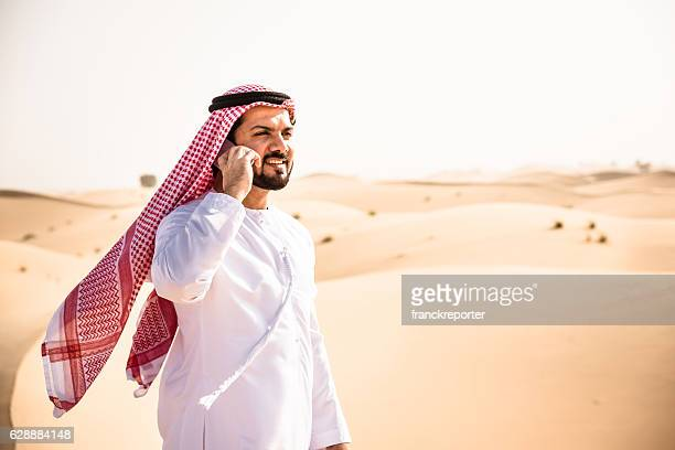 arabic sheik on the phone on the desert