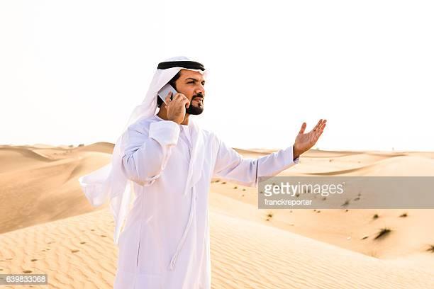 arabic sheik on the phone on the desert