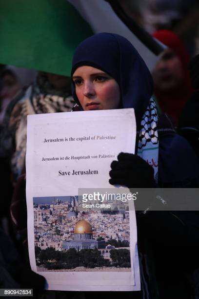 Arabicspeaking protesters including a young woman holding a photograph of the Dome of the Rock in Jerusalem attend a gathering to protest against the...