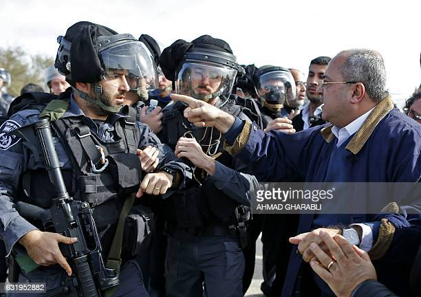 TOPSHOT ArabIsraeli Knesset members Ahmad alTibi confronts an Israeli policeman during clashes with Bedouin protesters in the village of Umm alHiran...