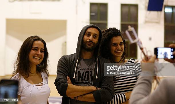 ArabIsraeli rapper Tamer Nafar poses for a picture with two female audience members after a performance during a festival in the northern ArabIsraeli...