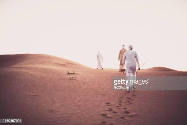 les arabes escaladent les dunes de sable - petit groupe de personnes photos et images de collection