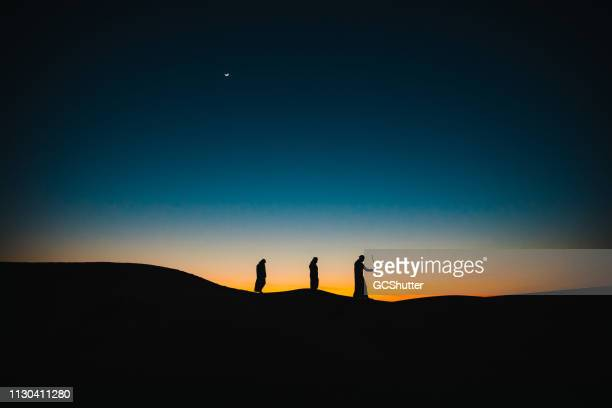 arabs on the sand dunes walking behind each other during twilight - eid mubarak stock pictures, royalty-free photos & images