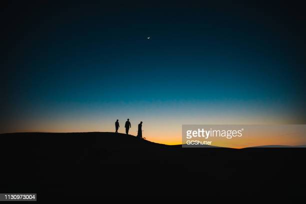 arabs on the sand dunes walking behind each other during twilight - ramadan stock pictures, royalty-free photos & images