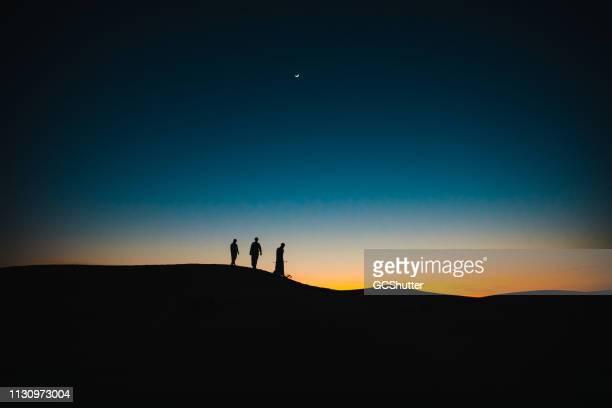 araber auf den sanddünen, die in der dämmerung hintereinander laufen - ramadan stock-fotos und bilder