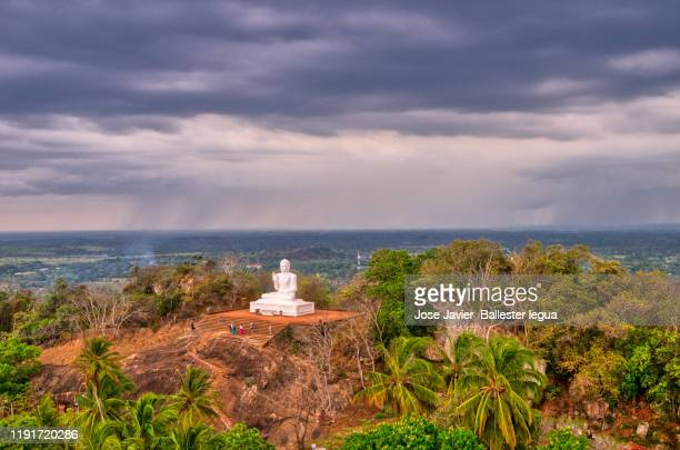 aradhana gala, an ancient rock shrine at mihintale, sri lanka, near of the ambasthale dagoba statue of buddha, - mihintale stock pictures, royalty-free photos & images