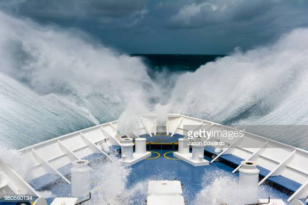 The bow of an expedition ship plows through breaking waves in the open sea.