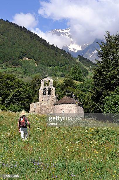 Aragnouet HautesPyrenees department 'Chapelle des Templiers' chapel and view of the 'Pic de Campbieil' mountain Pilgrim walking in the mountain