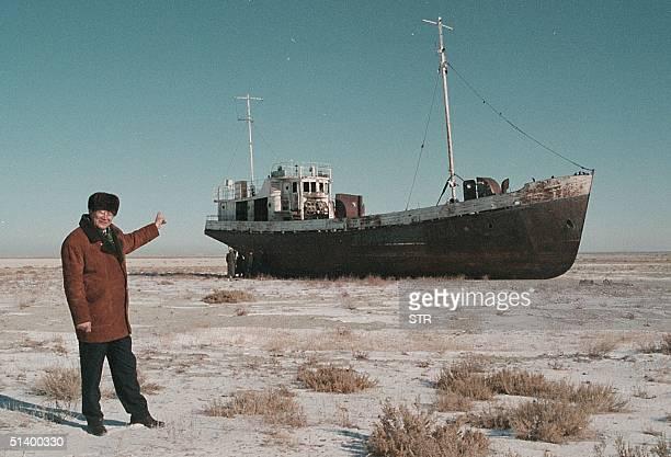 Aralsk's Mayor Alashbai Baimyrzayev points 23 March 1999 near the city of Kyzmet a fishery on Aralsk's dry harbor at an abandoned fishermen ship in...