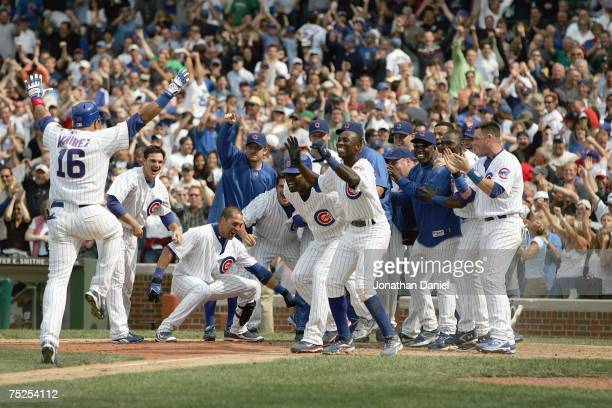 Aramis Ramirez of the Chicago Cubs run to home plate where he is greeted by teammates after Ramirez hit a tworun walkoff home run to beat the...