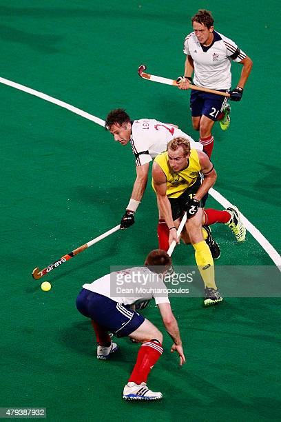 Aran Zalewski of Australia battles for the ball with Henry Weir Iain Lewers and Tim Whiteman of Great Britain during the Fintro Hockey World League...